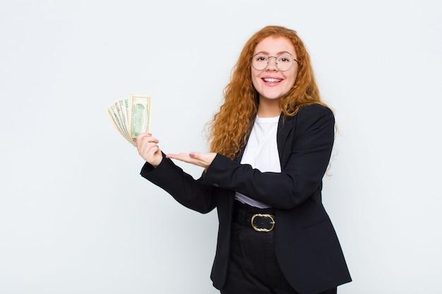 赤い頭の若い女性が元気に笑顔、幸せを感じて、白い壁に手のひらでコピースペースの概念を示す