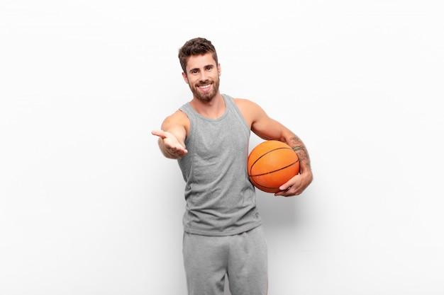 笑みを浮かべて、幸せで自信を持って、フレンドリーな若いハンサムな男、ハンドシェイクを提供して、契約を結ぶためにバスケットボールのボールを持って協力します。