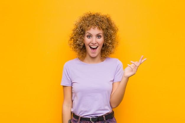 幸せ、驚き、陽気、前向きな姿勢で笑顔、オレンジ色の壁に対する解決策またはアイデアを実現している若いアフロ女性