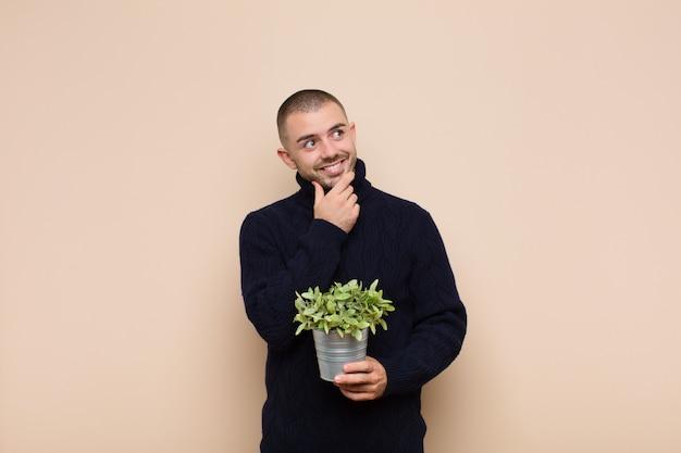 幸せそうに笑って、空想にふけったり、疑ったり、植物を保持している側を探している若いハンサムな男