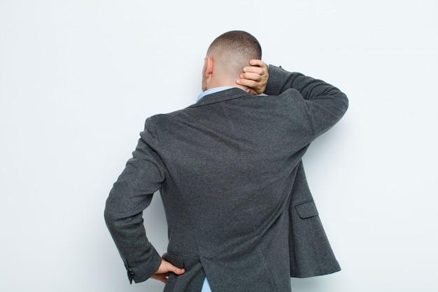 青年実業家思考または疑い、頭を掻く、困惑し、混乱している、平らな壁に対して背面または背面ビュー