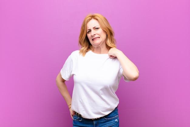 ストレス、不安、疲れ、欲求不満を感じ、シャツの首を引っ張って、問題で欲求不満に見える中年女性
