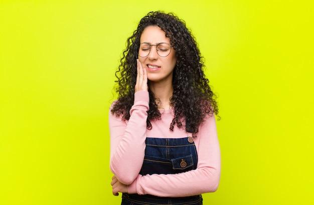 若いきれいな女性の頬を押し、痛みを伴う歯痛に苦しんでいる、気分が悪く、悲惨で不幸な、クロマキーの壁に歯医者を探している