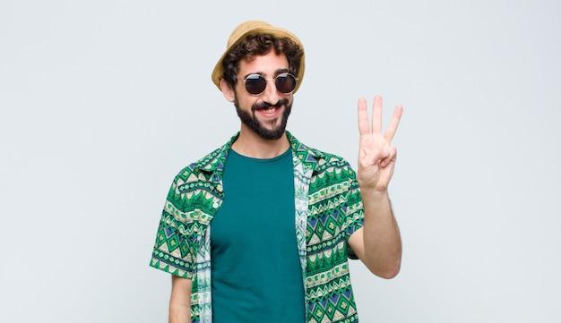 Молодой турист человек улыбается и смотрит дружелюбно, показывая номер три или третий с рукой вперед, считая вниз против белой стены