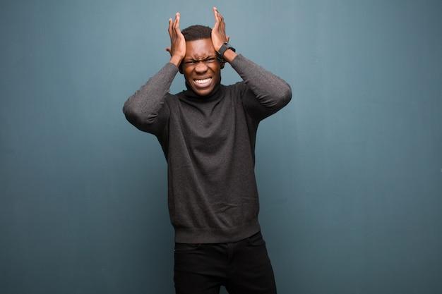Молодой человек чувствует стресс и беспокойство, депрессию и разочарование от головной боли, поднимая обе руки к стене гранж