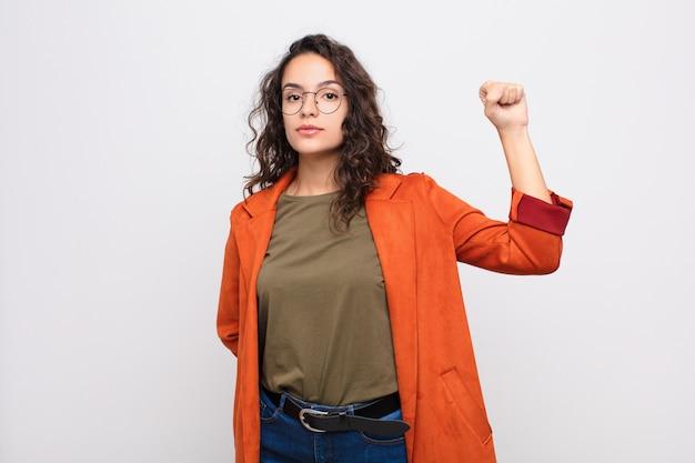 若いきれいな女性が深刻な、強くて反抗的な感じ、拳を上げる、抗議または白い壁に対する革命のために戦う
