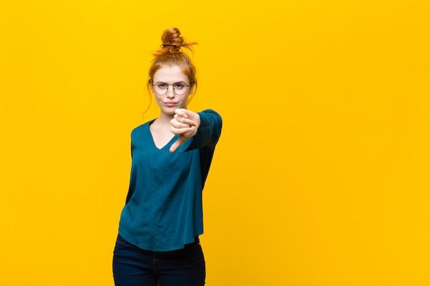 オレンジ色の壁に真剣な表情で親指を下に見せてクロス、怒り、イライラ、失望、または不満を感じている若い赤い頭の女性