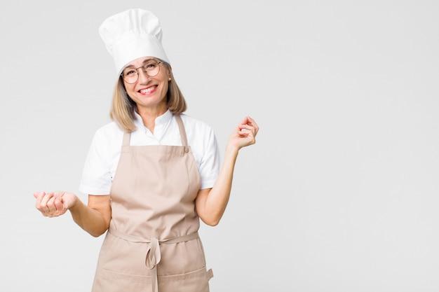 中年のパン屋の女性笑顔、屈託のない、リラックスした、幸せな、ダンス、音楽を聴く、平らな壁のパーティーで楽しんで