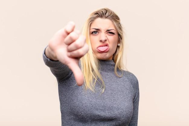 壁に深刻な表情で親指を下に見せてクロス、怒り、イライラ、失望、または不満を感じている若いかなりブロンドの女性