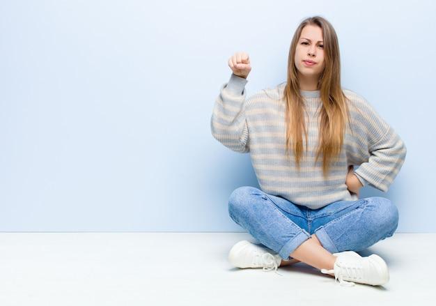 深刻な、強くて反抗的な感じ、拳を上げる、抗議または床に座っている革命のために戦う若いブロンドの女性