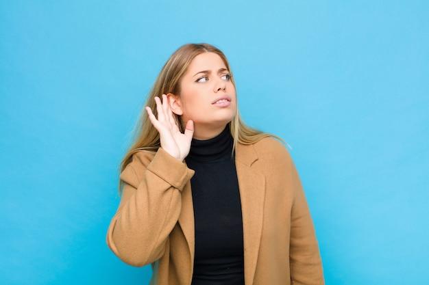 Молодая блондинка выглядит серьезной и любопытной, слушая, пытаясь услышать секретный разговор или сплетни, подслушивая у стены