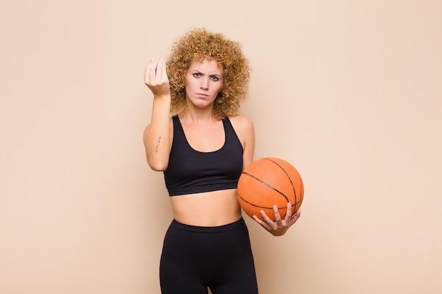 Молодая афро женщина, делающая жест капитана или деньги, говорит вам, чтобы расплатиться с долгами! спортивная концепция