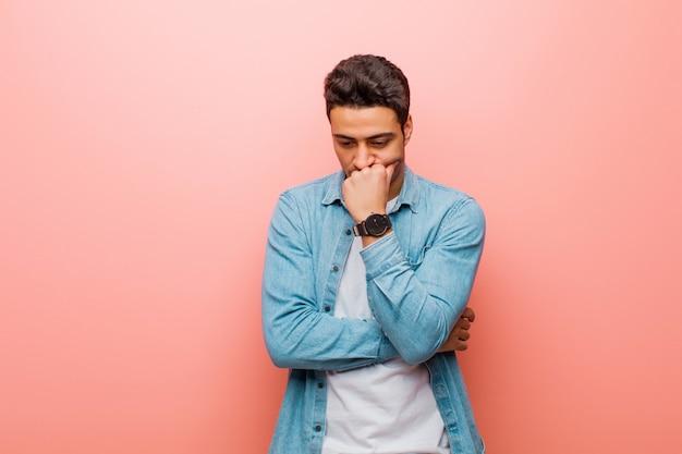 若い男がピンクの壁に対してあごに押し付けられた手で横をじっと見つめて、深刻で思慮深く心配していると感じている