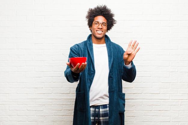朝食ボウルとパジャマを着ている若い黒人男性
