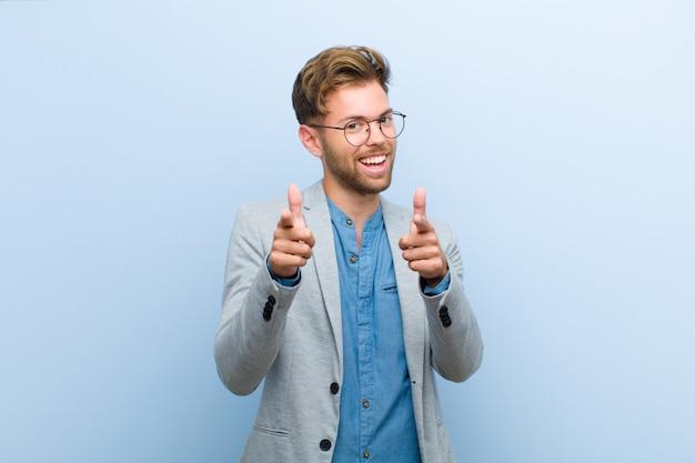 Молодой предприниматель, улыбаясь с положительным, успешным, счастливым ориентацией, указывая, делая пистолет знак руками против голубой стены