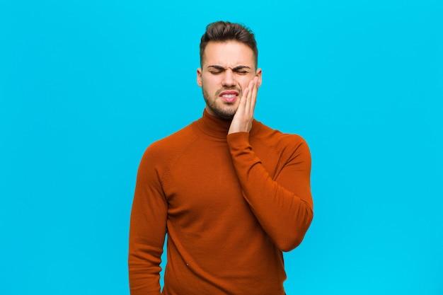 ヒスパニック系の若い男が頬を押し、痛みを伴う歯痛に苦しんで、気分が悪く、悲惨で不幸になって、青い壁に歯医者を探している