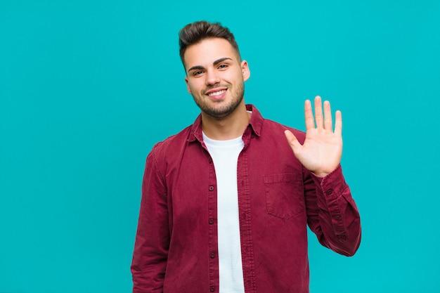 ヒスパニック系の若い男が幸せそうに笑って、手を振って、歓迎して挨拶するか、青い壁に別れを告げる