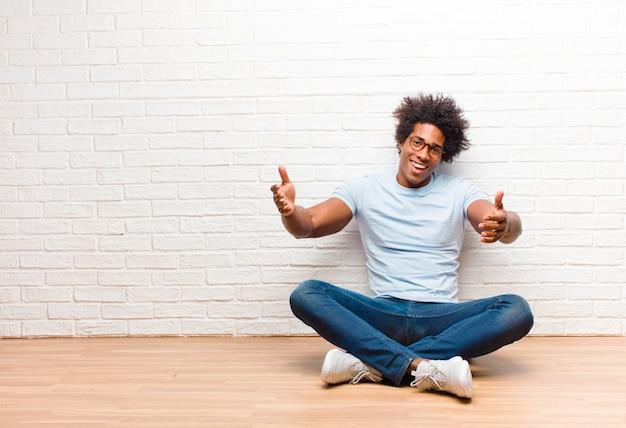 若い黒人男性が元気に暖かく、フレンドリーで、愛情のこもった歓迎抱擁を与えて笑顔で、家の床に座って幸せで愛らしい