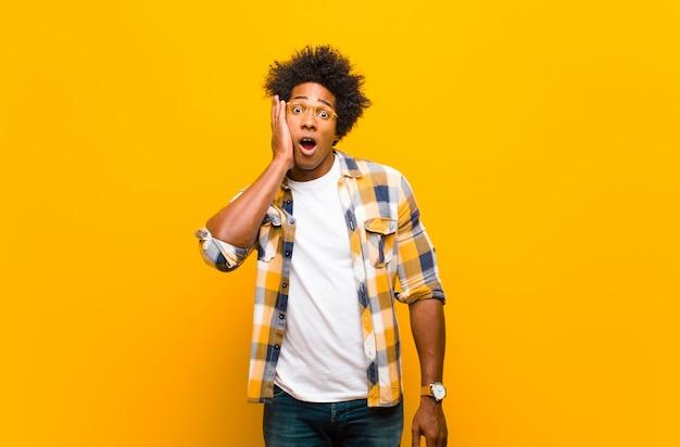 オレンジ色の壁に口を大きく開けて、信じられない思いで手に顔を抱えてショックを受け、驚いた若い黒人男性