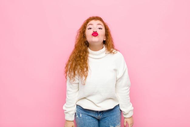 Молодая рыжеволосая женщина сжимает губы вместе с милым, веселым, счастливым, милым выражением лица, посылая поцелуй через розовую стену