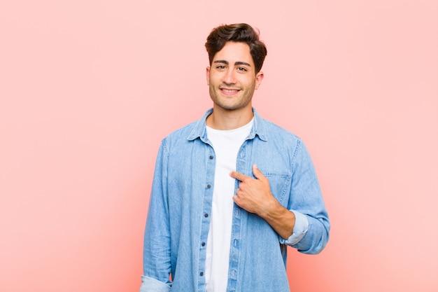 Молодой красавец выглядит счастливым, гордым и удивленным, весело указывая на себя, чувствуя себя уверенно и возвышенно над розовой стеной