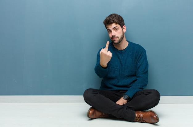 Молодой красивый мужчина, сидящий на полу, чувствуя себя злым, раздраженным, мятежным и агрессивным, щелкает средним пальцем и сопротивляется