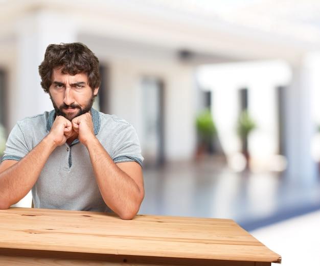 テーブルの上に若い男。心配表現