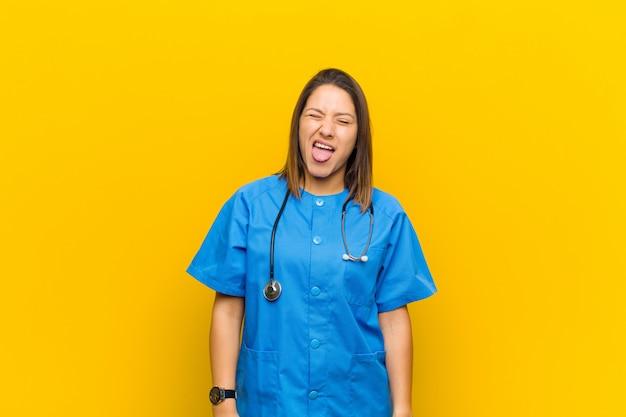 陽気でのんき、反抗的な態度で、冗談を言って舌を突き出し、黄色の壁に孤立して楽しんでいる