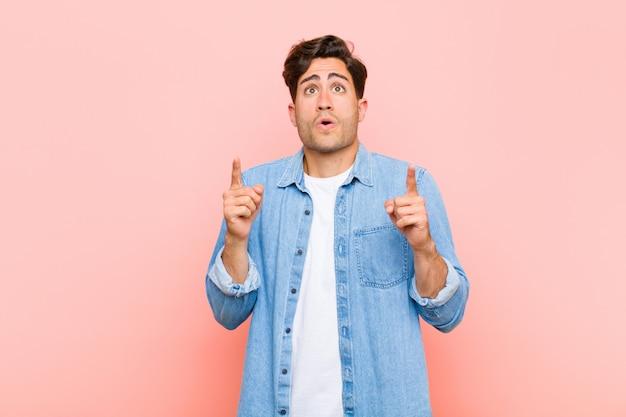 Молодой красивый мужчина, выглядящий потрясенным, пораженным и открытым ртом, указывая вверх обеими руками, чтобы скопировать пространство на фоне розового
