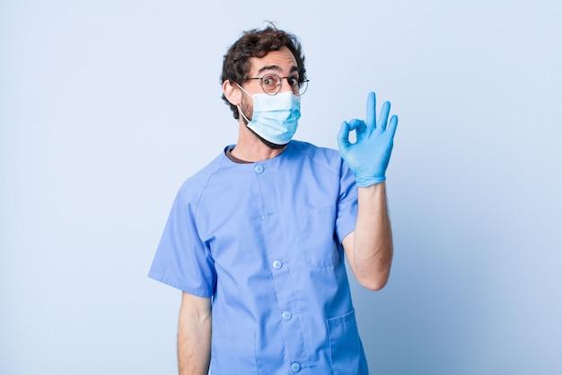 Молодой человек чувствует себя успешным и довольным, улыбаясь с широко открытым ртом, делая хорошо знаком с рукой. концепция коронавируса