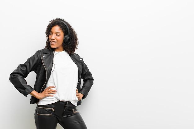 白い壁に革のジャケットを着てヘッドフォンで音楽を聴く若いきれいな女性