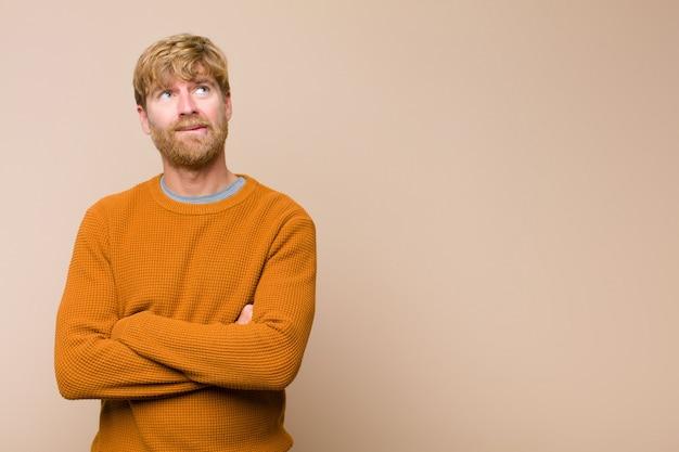 Молодой блондин сомневается или думает, кусая губу и чувствуя себя неуверенно и нервно, пытаясь скопировать пространство на плоской стене