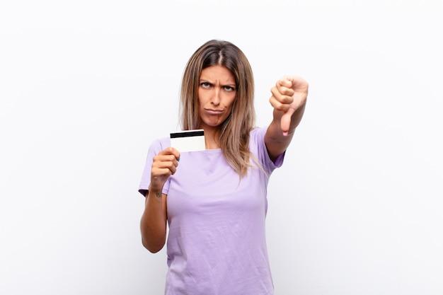 クレジットカードで深刻な表情で親指を下に見せて、怒り、イライラ、失望、または不満を感じている若いきれいな女性