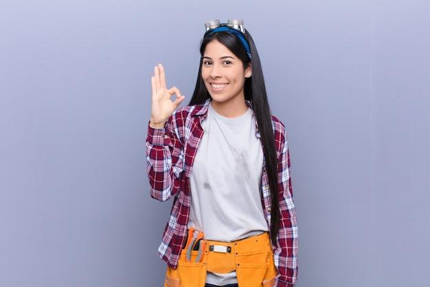 幸せ、リラックス、満足を感じて、大丈夫のジェスチャーで承認を示す、笑顔の若いラテン女性