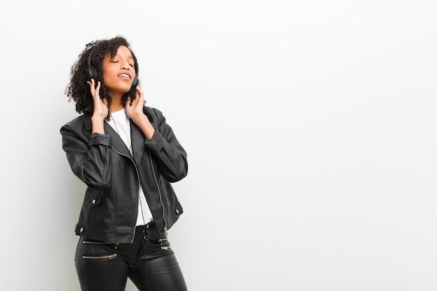白い壁に革のジャケットを着てヘッドフォンで音楽を聴く若いかなり黒人女性