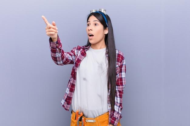 ショックを受けて驚いた若いラテン女性、驚いて口を開けた表情で畏敬の念を向け、指さして上向きに