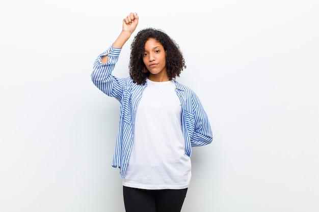 若いクールなアフリカ系アメリカ人女性は深刻な、強くて反抗的な感じ、拳を上げる、抗議または革命のために戦う