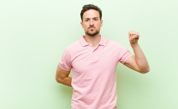 若いハンサムな男が深刻な、強くて反抗的な感じ、拳を上げる、抗議または革命のために戦う