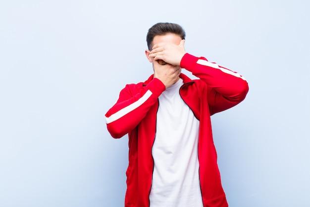 若いハンサムなスポーツマンまたはモニターは両手で顔を覆ってノーと言っています!平らな壁で写真を拒否したり写真を禁止したりする