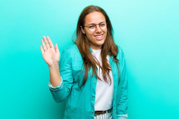 若い女性が楽しく、元気に笑みを浮かべて、手を振って、歓迎して挨拶、または青い背景に対してさようならを言う