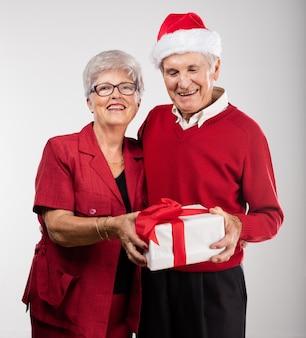 Пожилая пара улыбаясь с подарком