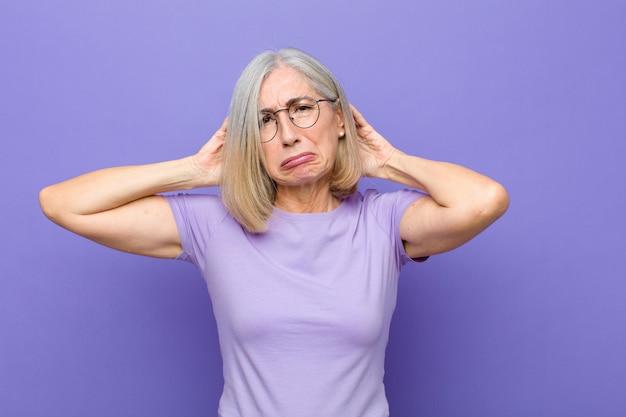シニアまたは中年のきれいな女性は、欲求不満でイライラし、病気で疲れて疲れ、退屈で退屈な仕事にうんざりしています