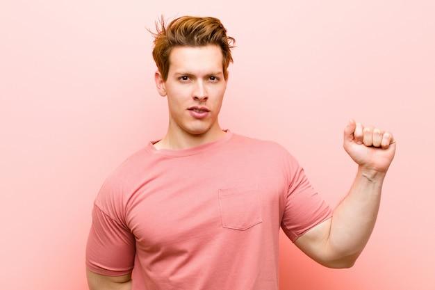 真面目で力強く反抗的な感じの拳を上げる、抗議する、またはピンク色の壁に対する革命のために戦う若い赤い頭の男