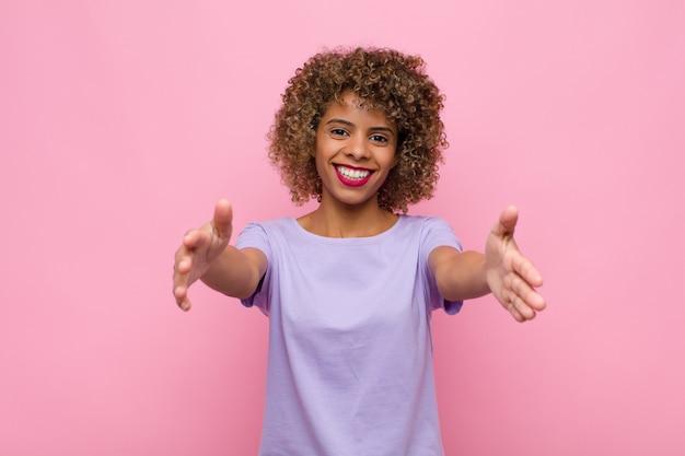 Молодая афроамериканская женщина весело улыбается, давая теплые, дружеские, любящие приветственные объятия, чувствуя себя счастливой и очаровательной на фоне розовой стены