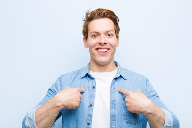 Молодой рыжий мужчина, чувствуя себя счастливым, удивленным и гордым, указывая на себя взволнованным, изумленным взглядом на синей стене