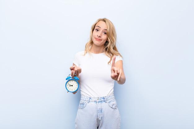 Молодая белокурая женщина гордо и уверенно улыбается, триумфально позируя номер один, чувствуя себя лидером, держащим часы