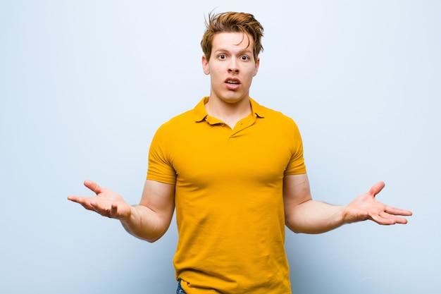 Молодой рыжеволосый мужчина с открытым ртом и изумлением, шоком и изумлением с невероятным сюрпризом на фоне голубой стены