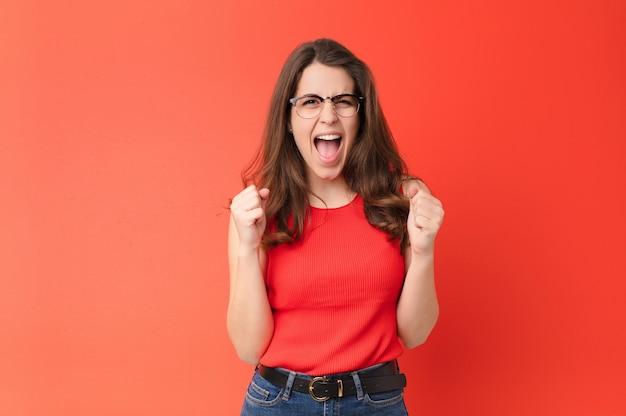 ショックを受け、興奮し、幸せで、笑い、成功を祝っている若いプリティウーマン、すごい!赤い壁の上
