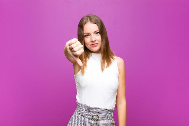 赤い頭のきれいな女性が紫の壁に対して深刻な表情で親指を下に見せて、怒り、イライラ、失望、または不満を感じている