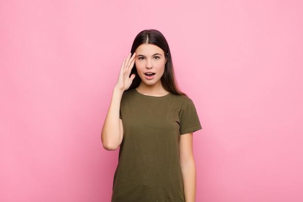 Молодая красивая женщина, глядя удивлен, с открытым ртом, шокирован, понимая новую мысль, идею или концепцию на фоне розовой стены